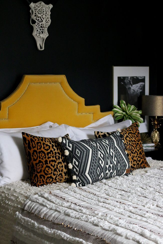 moroccan style wedding blanket with leopard print cushions in black bedroom with yellow headboard