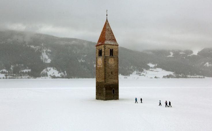 Church steeple peeking out of a frozen lake, Reschen, Italy