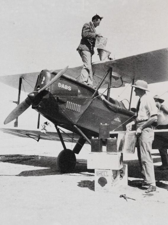 "4383B/290: H.F. (Jim) Broadbent (left) and Mr Durack refuel the Avro Avian IVM VH-UQE ""Dabs"" at Wyndham during his record round Australia flight, 3 September 1931.  http://encore.slwa.wa.gov.au/iii/encore/record/C__Rb4776724__Sw.a.%20airways%20airmail__Orightresult__U__X6?lang=eng&suite=def"