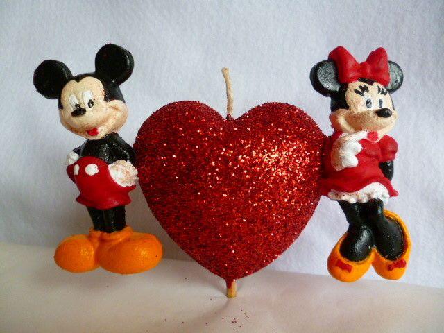 Vela em formato de coração, com acabamento em glitter vermelho, com o Mickey de um lado e a Minnie do outro, produzida com cera a base de óleo vegetal. <br>Possui um palito para que possa ser espetada no bolo, sem danificar a cobertura.