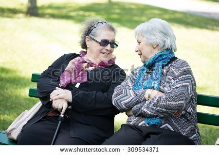 two seniot ladies talking friendly on a bench