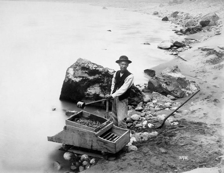 Photograph of a Chinese man washing gold in the Fraser River in 1875.