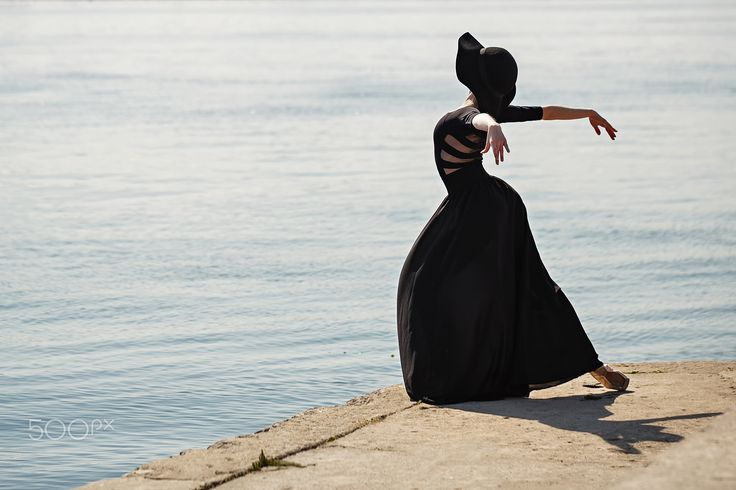 Ballerina in hat and long black dress beautiful dancing. - Young slender dancer in a hat and a long black dress dancing on a beautiful promenade. Summer day. The concept modern ballet. Performance on the street. Minimalism.