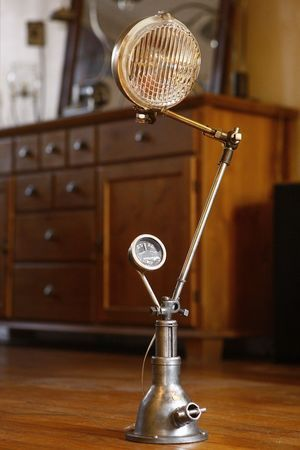 Lampe que j'ai créé avec un ancien cric de voiture, un phare de voiture, un manomètre de tableau de bord et des mécanismes récupérés sur un ancienne machine à coudre Singer.   Lamp that I created with an old car jack, a car headlight, a gauge dash and recovered on an old Singer sewing machine mechanisms.