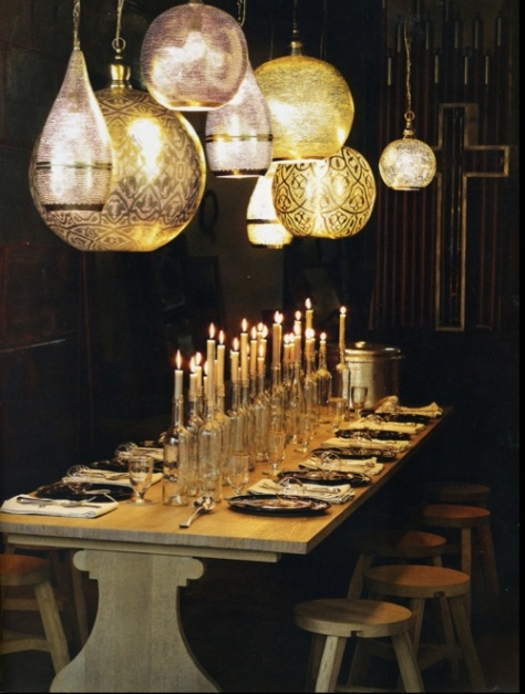 great ideas from Abigail Ahern:different height bottles and taper candles to create dramatic lighted centerpiece! I love her