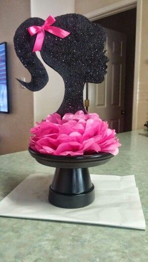 "Barbie centerpiece. The stand is a terra cotta pot and plate, spray painted black. The head is 2"" thick Styrofoam cut with a Styrofoam cutter from local craft store. Hand painted head with acrylic paint and added glitter. Tissue paper flower. Hot glue holding it all together."