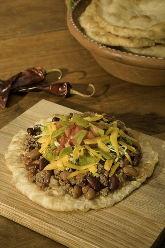 Bison Meat Navajo Indian Tacos from the Meat Chapter of the Taco Table Cookbook.  Featured in this photo is a bison meat Indian taco featuring organically raised local bison with organic beans, green chile, cheese, lettuce, tomato on a piece of homemade fry bread.