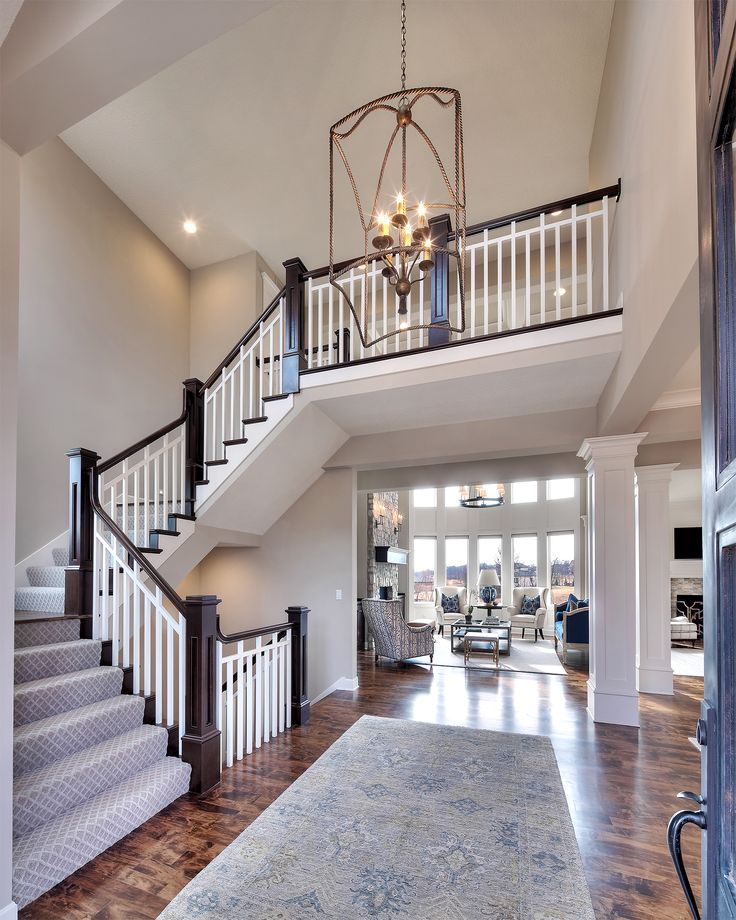 Entry curved staircase open floor plan overlook from for Sycamore interior designs