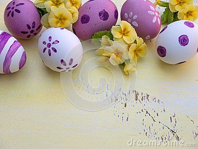 Violet Easter eggs and primrose flowers bouquet composition