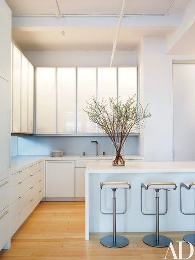 The kitchen's upper cabinets feature custom-made Häfele doors of anodized aluminum and acrylic; the lower cabinetry is Corian by DuPont. The dishwasher is by Bosch, the Elio sink fittings are by Dornbracht, and the barstools are by Lapalma | archdigest.com