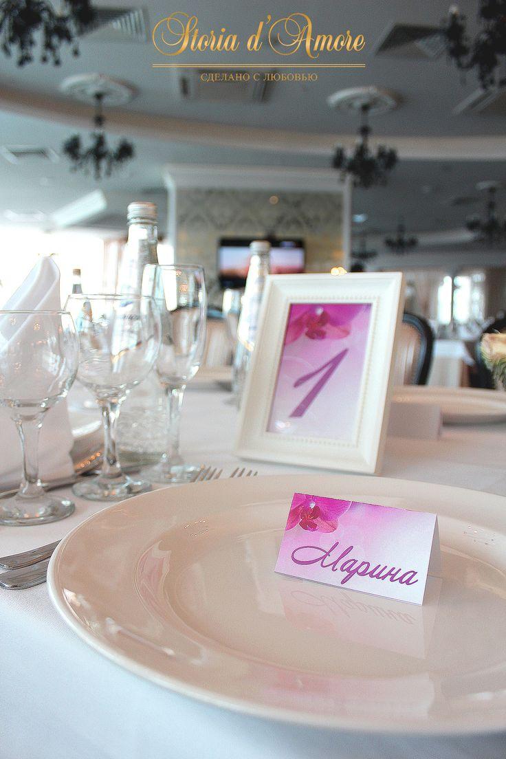 Номерки на столы и банкетные карточки тоже украшены орхидеями.