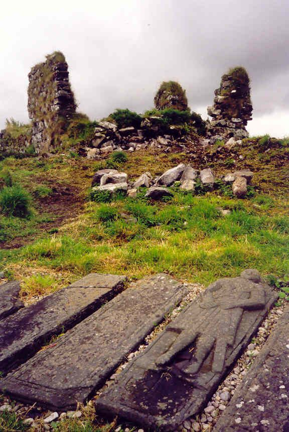 Finnlagen Castle in back, old tombstones in forground of members of the family of the chifetens of clan McDonald,clan McRanald.