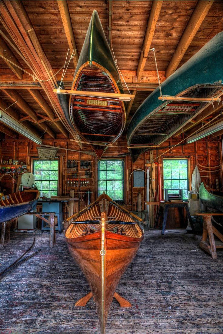 Inside the Boatshop at Great Camp Sagamore. A guideboat on the main floor and two wood and canvas canoes above.