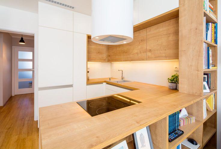 Dekor dubu na kuchyňských skřínkách i na knihovně interiér příjemně zatepluje.