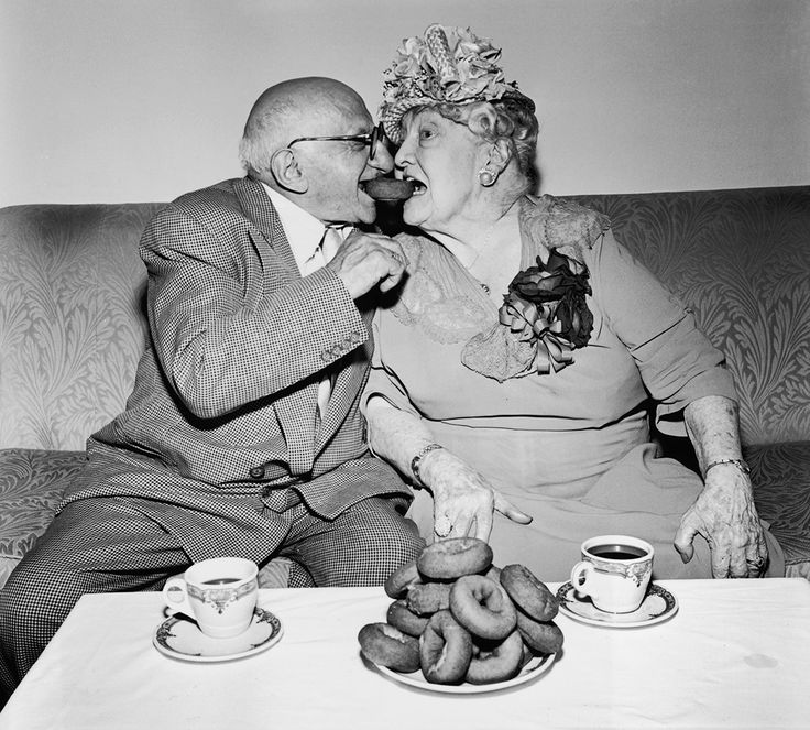 1953: An elderly man and woman pose while eating from opposite sides of the same donut, during a Donut Dunking Association meeting. They have a plate of donuts and two cups of coffee. (Photo by Hulton Archive/Getty Images)