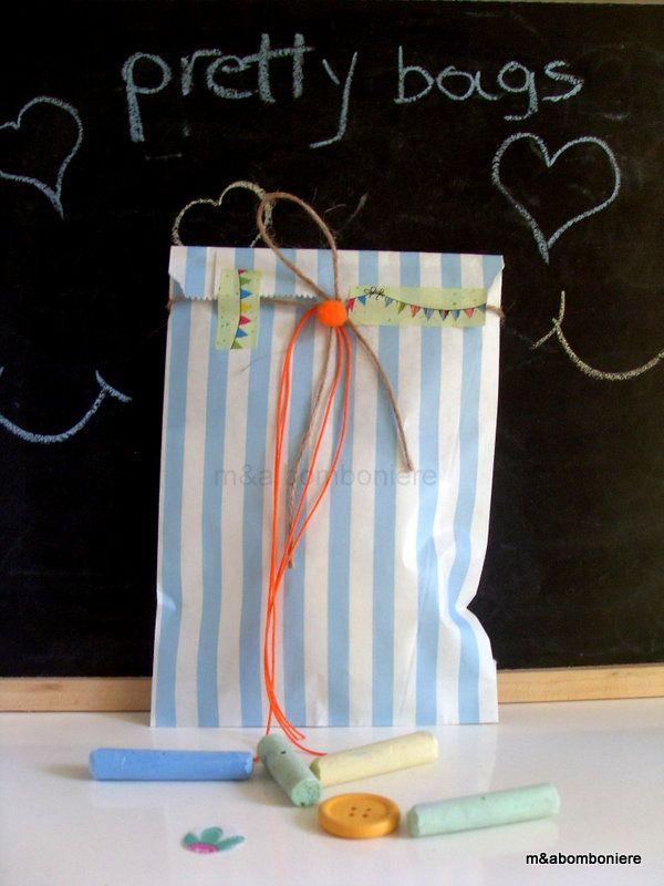 Γαλάζιο ριγέ σακουλάκι με σχοινάκι και πορτοκαλί κορδονάκι. Ένα πορτοκαλί πομ πομ και washi tape. Τιμή: 1,50 ευρώ.