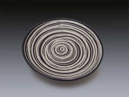 """A large, one of a kind, wheel-thrown shallow bowl of white stoneware, with sgraffito decoration. Clear glaze over black slip on interior which appears espresso. The exterior is black. Food-safe. 14"""" x"""