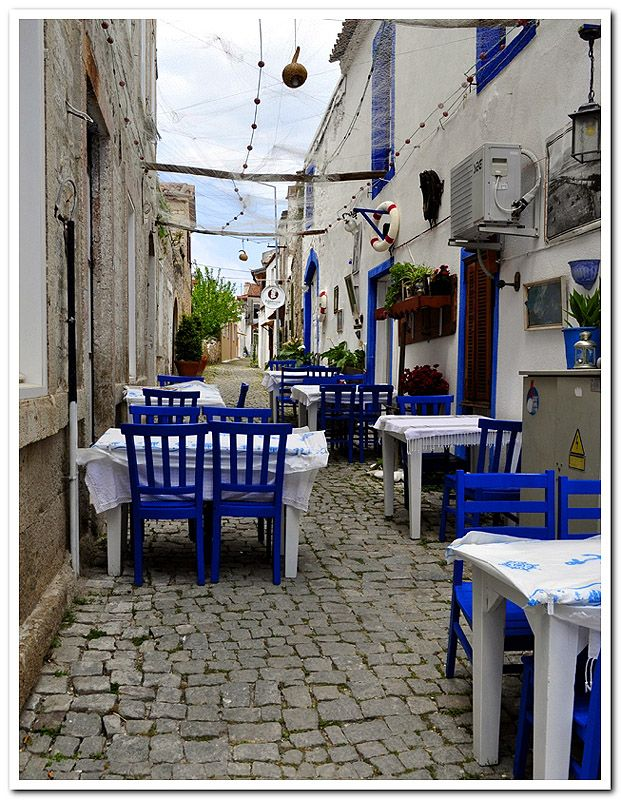 Blue chairs by mesutilgim: Another street szene from the famous Aegean summer resort Alacati close to Cesme. The restaurants are ready for the next summer and wait for their first customers. Alaçatı sokaklarından bir kare daha. Restoranlar yeniden badanalanmış, masa örtüleri tiril tiril; ilk müşterileri bekliyorlar.