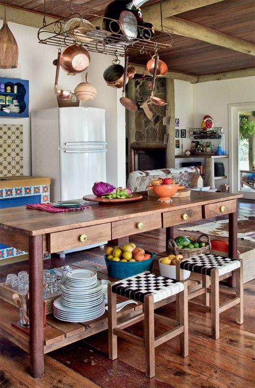 Casa de fazenda com panelas de cobre penduradas sobre a bancada na cozinha