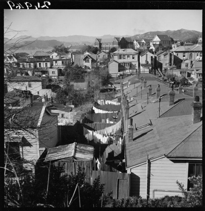 Ref: 1/4-001949-F  Backyards of houses in Thorndon, Wellington, New Zealand, with corrugated iron fences and rows of washing. Properties on the right face Aorangi Terrace. St Mary's College is in the background. Photograph taken by John Pascoe circa September 1944.