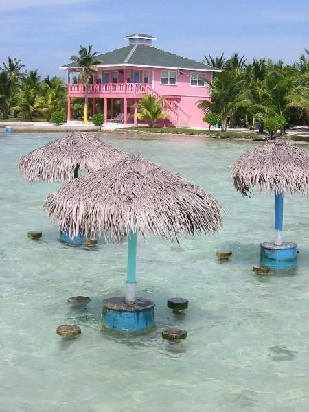 The swim up bar tables and pink guest house of Graham's Place in Guanaja, Honduras.