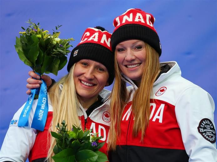 Kaillie Humphries and Heather Moyse (R) of Canada team 1 celebrate during the flower ceremony after winning the gold medal during the Women's Bobsleigh on Day 13 of the Sochi 2014 Winter Olympics at Sliding Center Sanki | Sochi 2014 Winter Olympics
