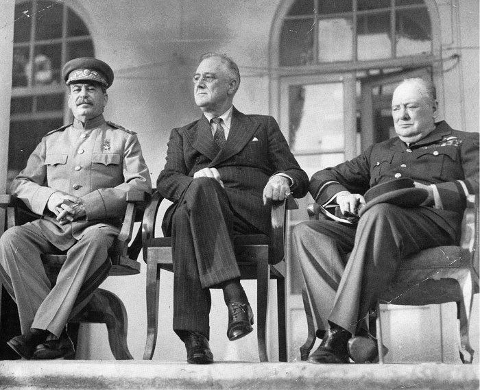 "28 November 1943. The ""Big Three"": From left to right: Joseph Stalin, Franklin D. Roosevelt, and Winston Churchill on the portico of the Russian Embassy during the Tehran Conference to discuss the European Theatre in 1943. Churchill is shown in the uniform of a Royal Air Force air commodore."