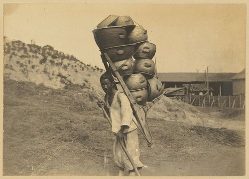 [Porter carrying clay pots strapped to A-frame on his back] by Cornell University Library, via Flickr