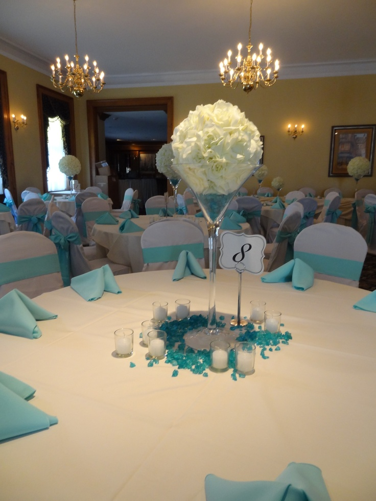 Oversize martini glasses with white flower orbs create a simple, yet elegant centerpiece. Sprinkle Tiffany Blue stones on the table and surround them with votives to add color to the white table and create ambiance.
