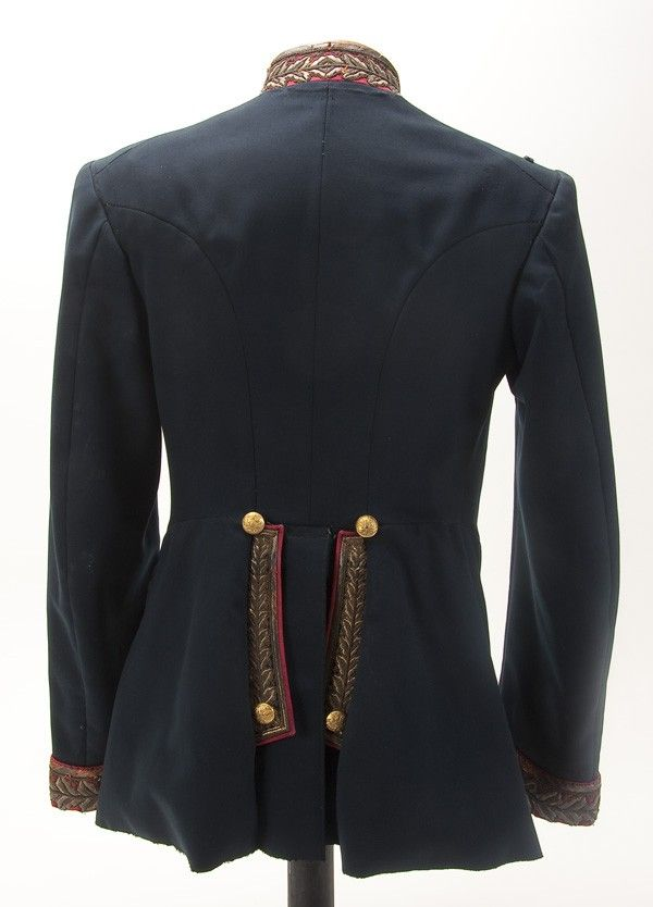 Back side view of an Imperial Russian unassigned General officer's tunic, circa 1900. Dark blue wool double breasted tunic with red collar, cuffs and piping. Collar and cuffs richly embroidered in a gold bullion oak leaf motif. Left chest with several worked holes for badges or orders, lacks epaulettes.