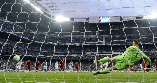 Real Madrid's Portuguese forward Cristiano Ronaldo scores a penalty against Bayern Munich's goalkeeper Manuel Neuer (R) during the UEFA Champions League second leg semi-final football match Real Madrid against Bayern Munich at the Santiago Bernabeu stadium in Madrid on April 25, 2012.