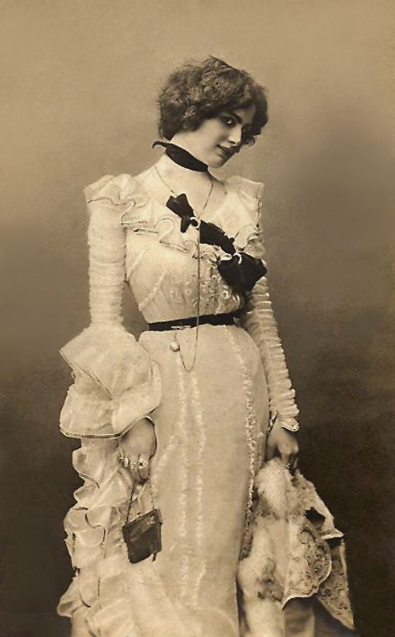 Lots of unusual details from the ribbon around her neck, to the multiple large rings, to the difference in the sleeves.