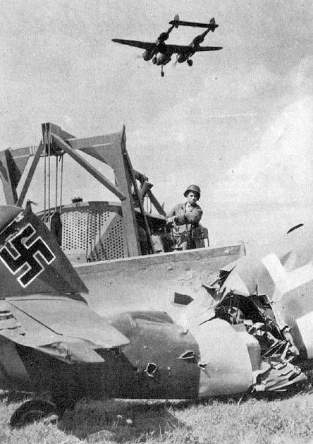 USAAF Engineer clearing out the wreckage of a Luftwaffe aircraft at an ALG with a P-38 Lightning flying overhead on landing approach