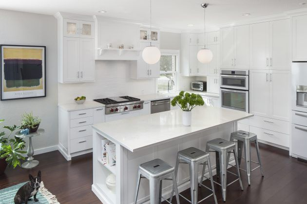 Calling all fans of white kitchens – Jameson Interiors is showing how it's done! The white cabinets are broken up with stainless steel appliances and light veining in the Frosty Carrina countertops.