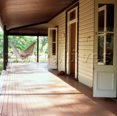 Wood panelled colonial country style house with large veranda French windows and a hammock in dapple