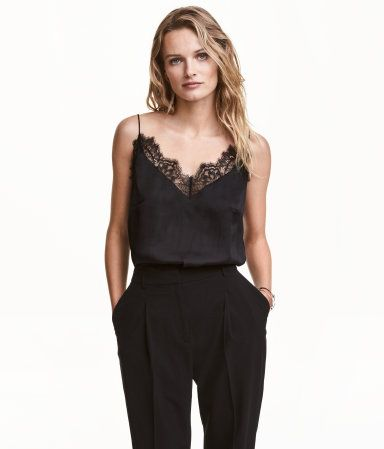 Black. Camisole top in airy satin with narrow shoulder straps, V-neck at front, and lace-covered edges.