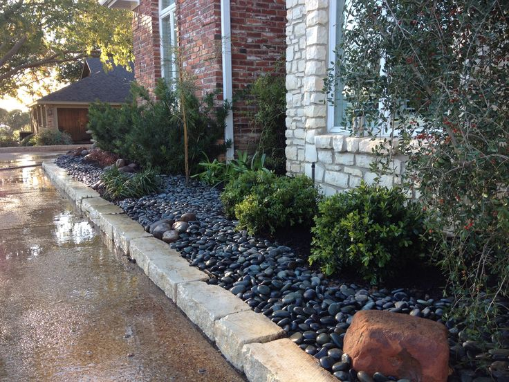 Here we used river rock instead of mulch. Makes for a dramatic look accented by boulders.