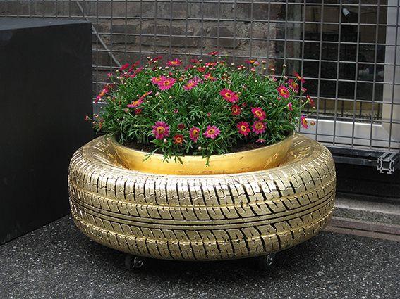 Fioriere realizzate con pneumatici rivestiti in foglia oro.