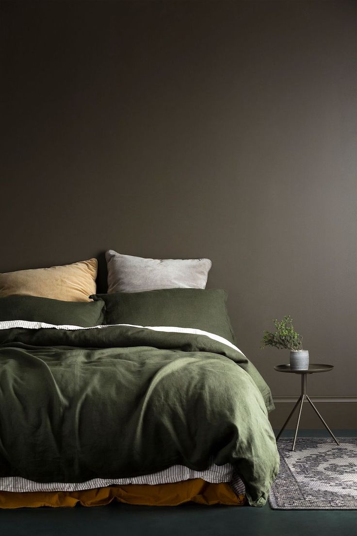 love this muddy brown feature wall and olive green bedding such a warm palette