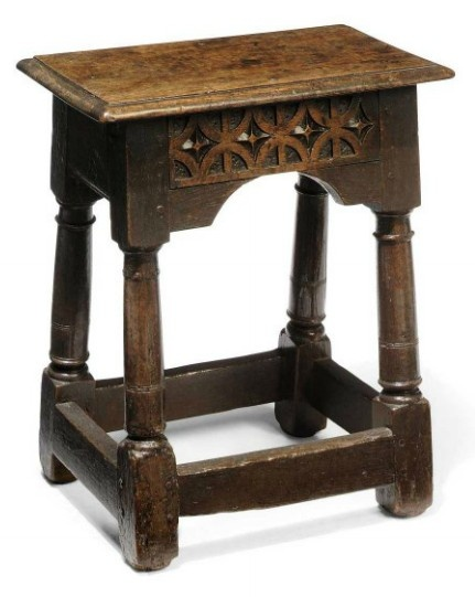 A CHARLES I OAK JOINED STOOL  EARLY 17TH CENTURY  With trellis pattern and spandrels to the long friezes, on ring-turned legs