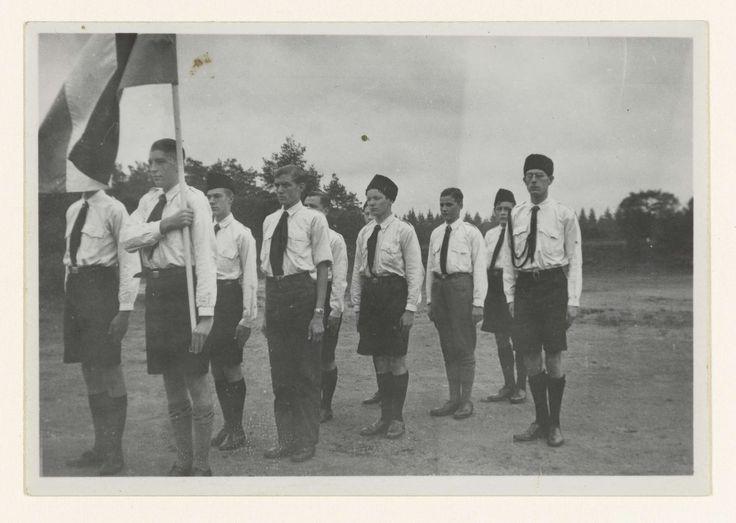 NSB | Jongens van de Jeugdstorm in het gelid met de Nederlandse vlag, NSB, Anonymous, 1934 - 1935 | Jongens van de Jeugdstorm staan in het gelid tijdens of na het afleggen van de gelofte op de Jeugdstorm tijdens hun installatie als lid. Links een lid met de Nederlandse vlag. Rechts staat een van de leiders van de Jeugdstorm. Op achterzijde foto: Installatie van troep I. ( Gelofte ). De foto maakt deel uit van een serie van circa 35 amateurfoto's.