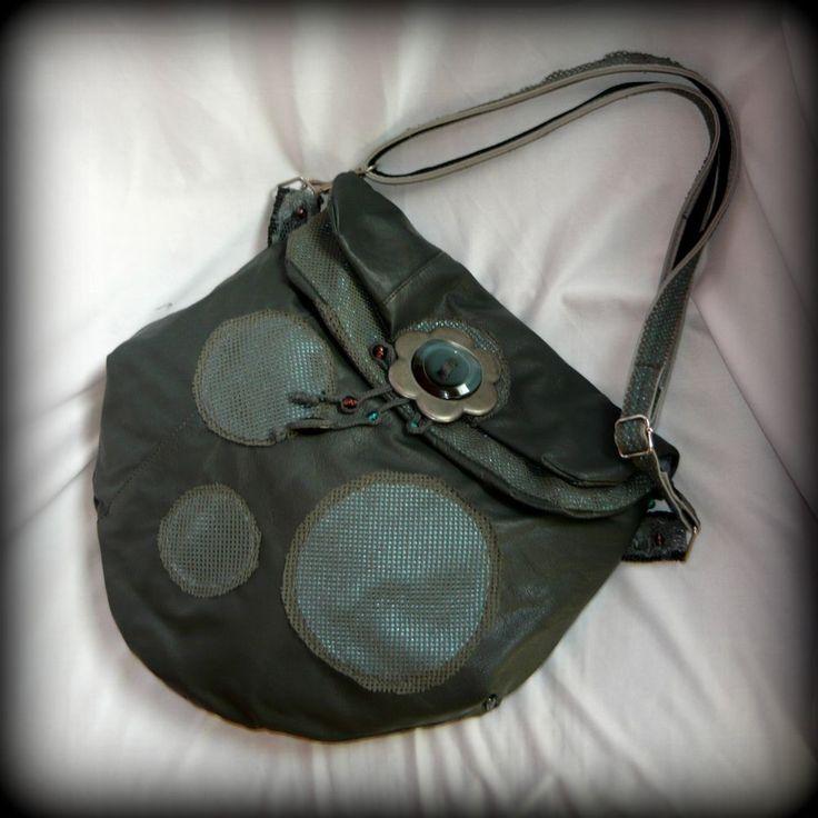 Szürke-kék pöttyös bőrtáska-handmade by Judy Majoros:A táska alapja valódi bőrből készült. Külsejét fényes türkiz textilbőr pöttyök díszítik, melyet szürke textilháló borít. Az elején található virágdísz ezüstös fém virágformából, egy nagy díszgombból, és gyöngyökből készült. A táska mágneszárral záródik. Belseje szürke és világoskék bélésselyemmel bélelt, díszített, valamint 2 zseb található benne. Pántja alapja műbőr, amit fényes kék textillel, és szürke hálóval díszítettem.