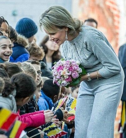 The glamorous Queen Mathilde of Belgium donned a stylish grey jumper adorned with shimmering sequins.  She matched her winter-themed jumper with a pair of light grey wide trousers and weighty drop earrings. Her highlighted hair was worn loosely for the informal occasion. Crowds of well-wishers gathered to meet the queen, handing her a pretty bouquet of pink flowers.