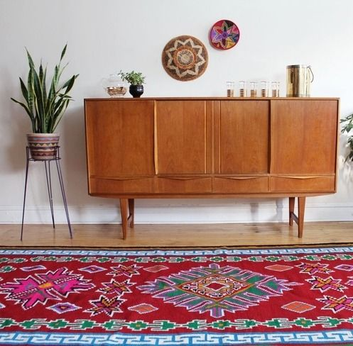 Large African area rug in bright and bold colors, with symmetrical handwoven patterns and a Greek key border.