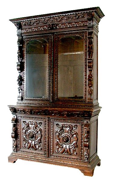 Monumental country French/Louis XVI style display cabinet. This antique cabinet is executed in heavily carved oak with glass doors on the upper portion opening to adjustable removable shelves circa 1870.