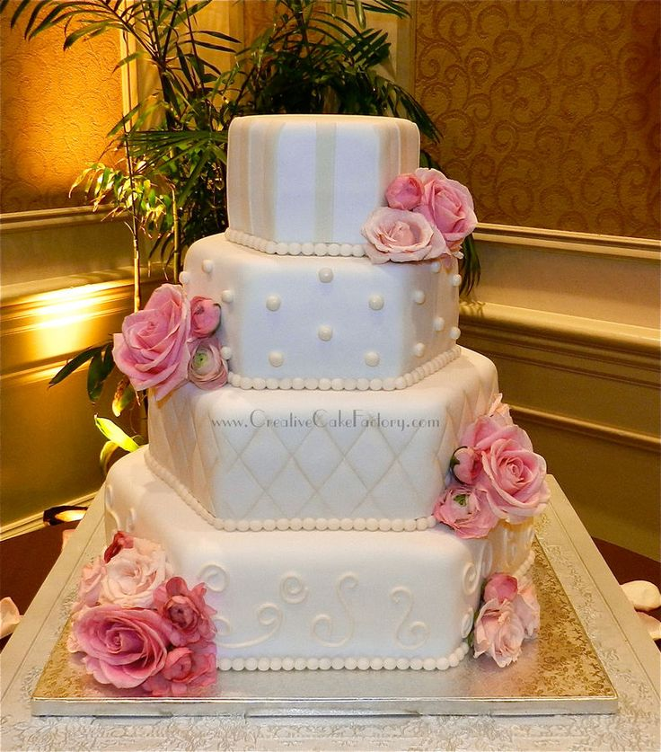 4 tier hexagon wedding cake. White fondant with ivory details. Fresh flowers.