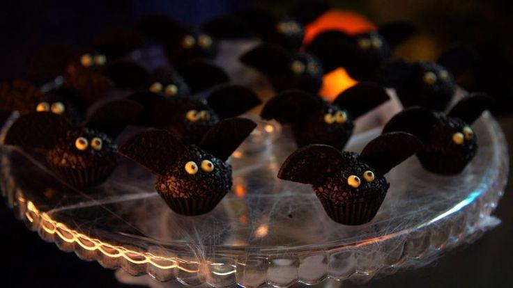 Receita com instruções em vídeo: As crianças vão amar e os adultos não vão resistir a esses deliciosos brigadeiros de morcego! Ingredientes: 395g (1 lata) de leite condensado, 2 colheres de sopa de cacau, 15g de manteiga, 125g de chocolate meio amargo + 1 colher de chá derretido, 100g de creme de leite, 100g de confeitos pretos, 20g de confeitos brancos de bolinhas, 100g de biscoito de chocolate sem recheio cortado ao meio