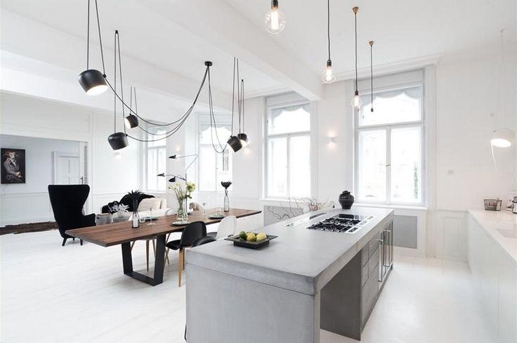 Dominantami obývacího prostoru jsou betonový ostrůvek a velký jídelní stůl.