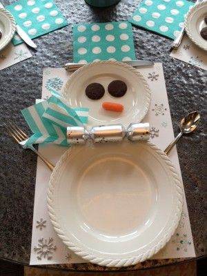 We used chocolate covered mint oreos for the eyes, a carrot for the nose, party crackers for the bow tie, dinner & cocktail napkins for the hat & scarf, our casual china for the snowman's body & head and silverware make up the arms & the brim on the hat.