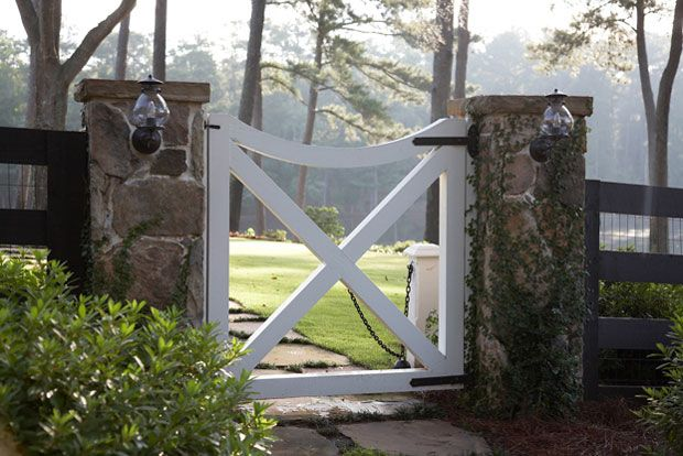 Love the stone columns with lights attached as well as the darling gate.